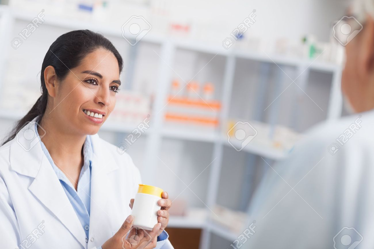Pharmacist holding a drug box while looking at a patient in hospital Stock Photo - 16204105