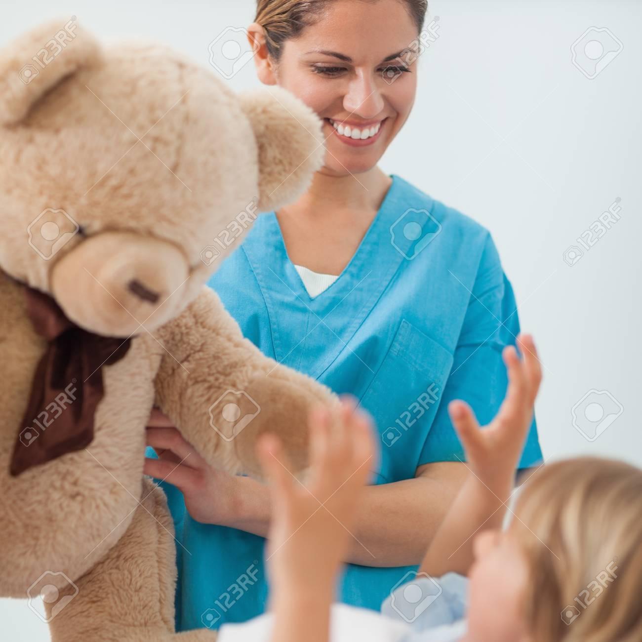 Smiling nurse holding a teddy bear in hospital ward Stock Photo - 16202421