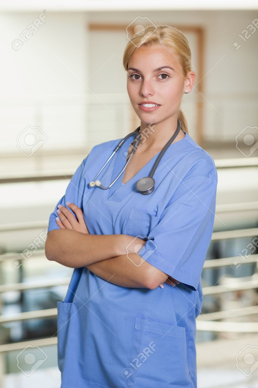 blonde nurse with arms crossed in hospital corridor stock photo