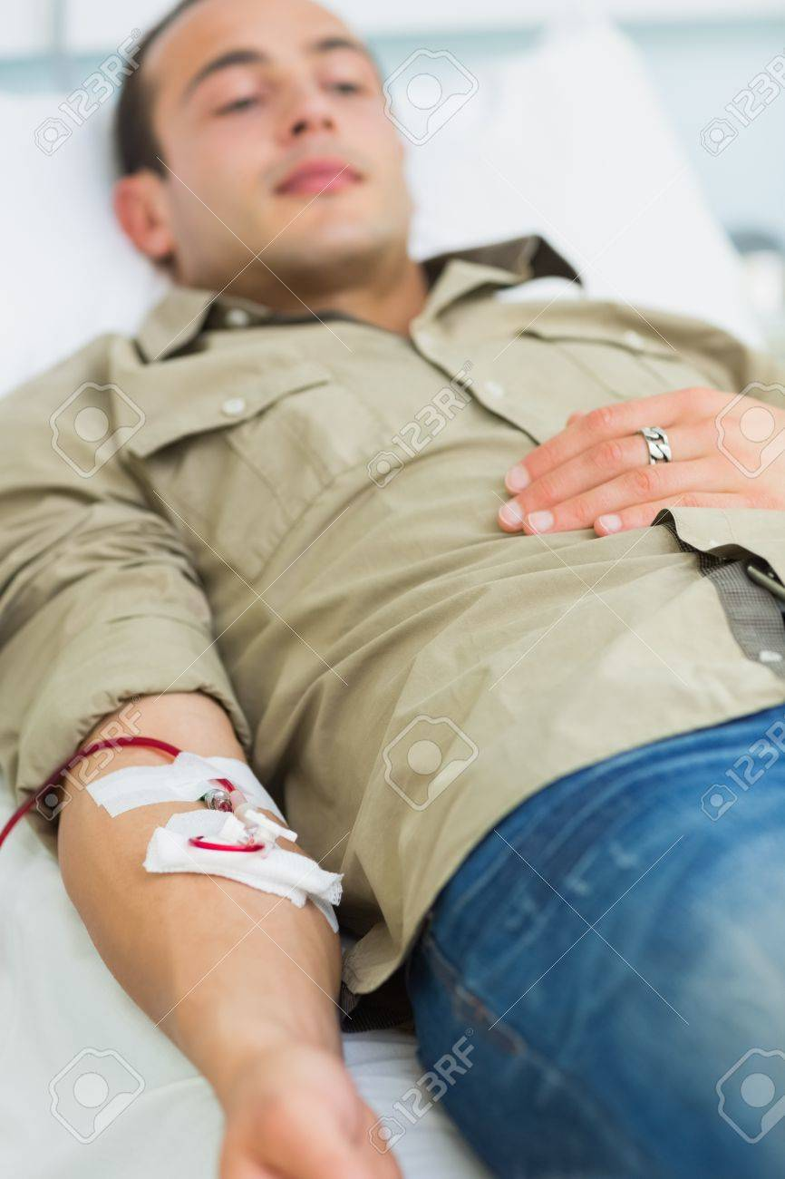 Male transfused lying on a bed in hospital ward Stock Photo - 16207316