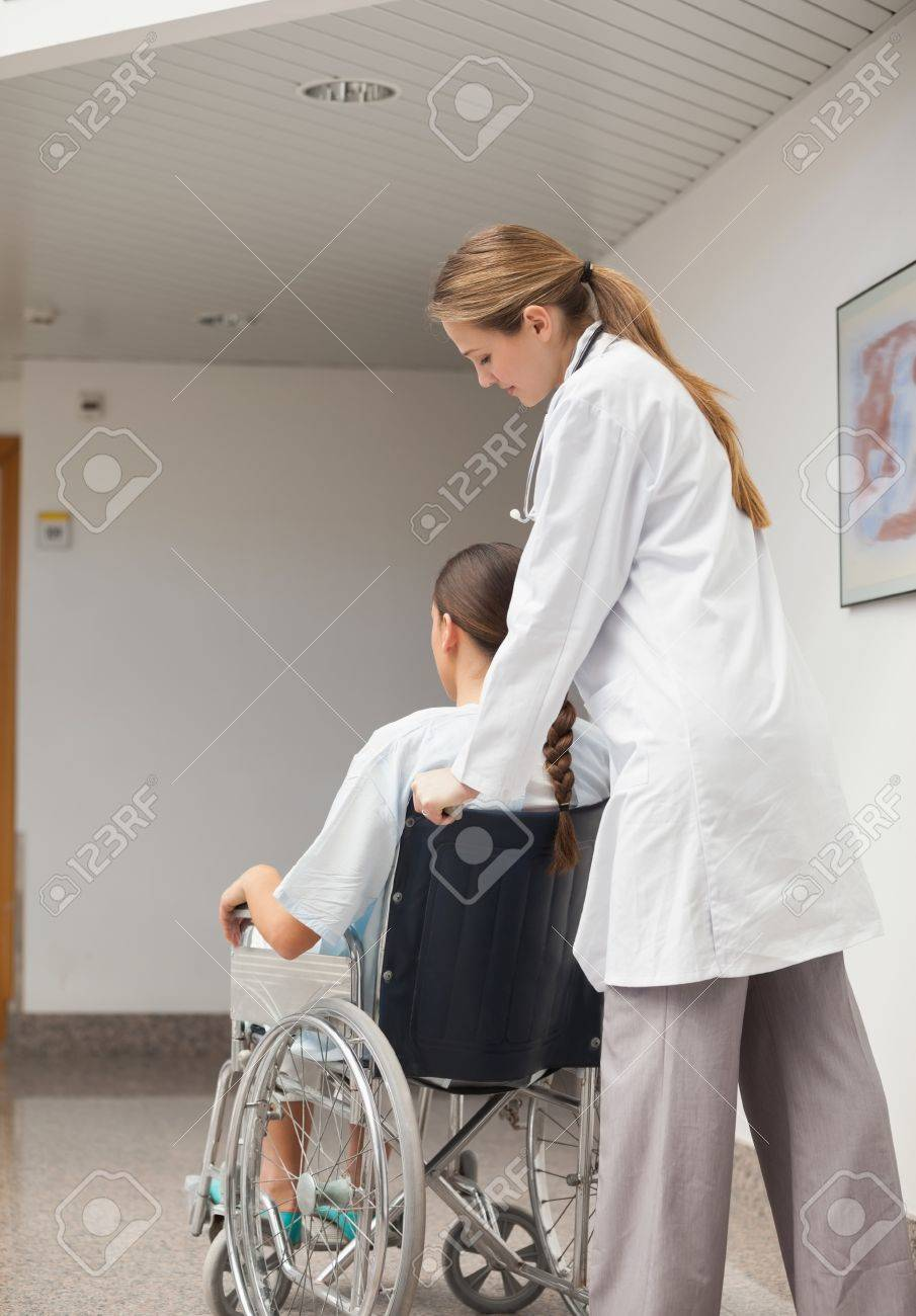 Doctor pushing a wheelchair in hospital ward Stock Photo - 16204672