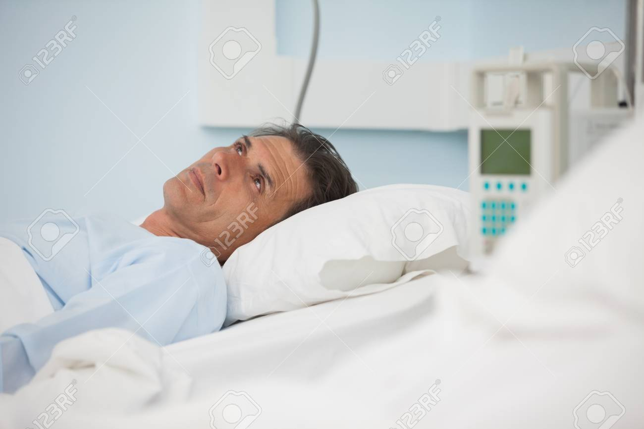 Thoughtful patient lying on a medical bed in hospital ward Stock Photo - 16202715