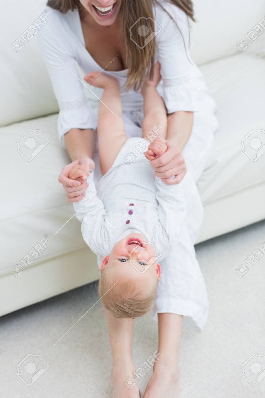 Mother sitting on a sofa playing with a baby in living room Stock Photo - 18682958