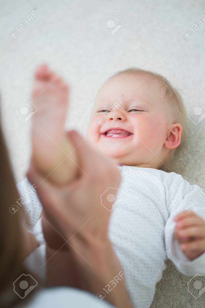 Mother raising the leg of a baby in living room Stock Photo - 16207303