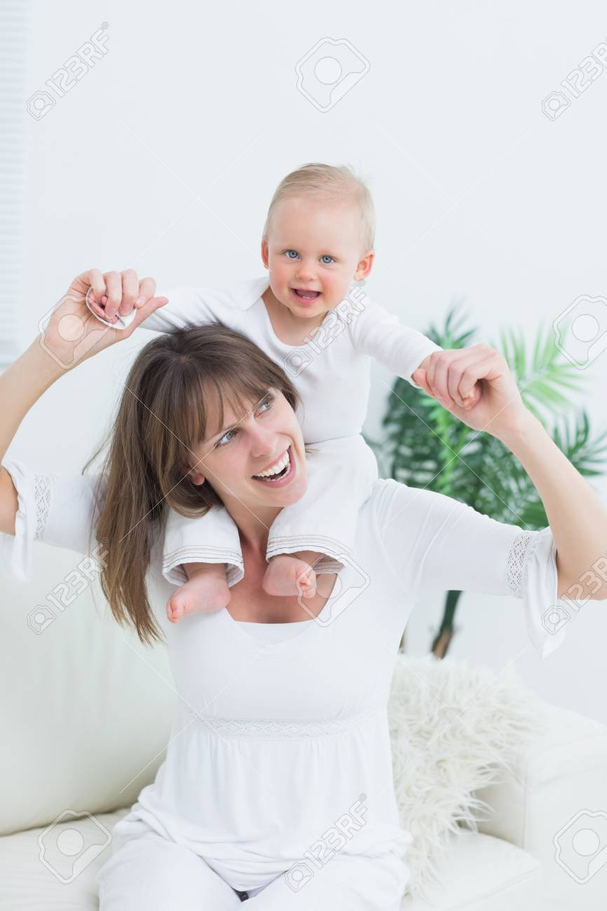 Baby sitting on shoulders of his mother in living room Stock Photo - 16203909