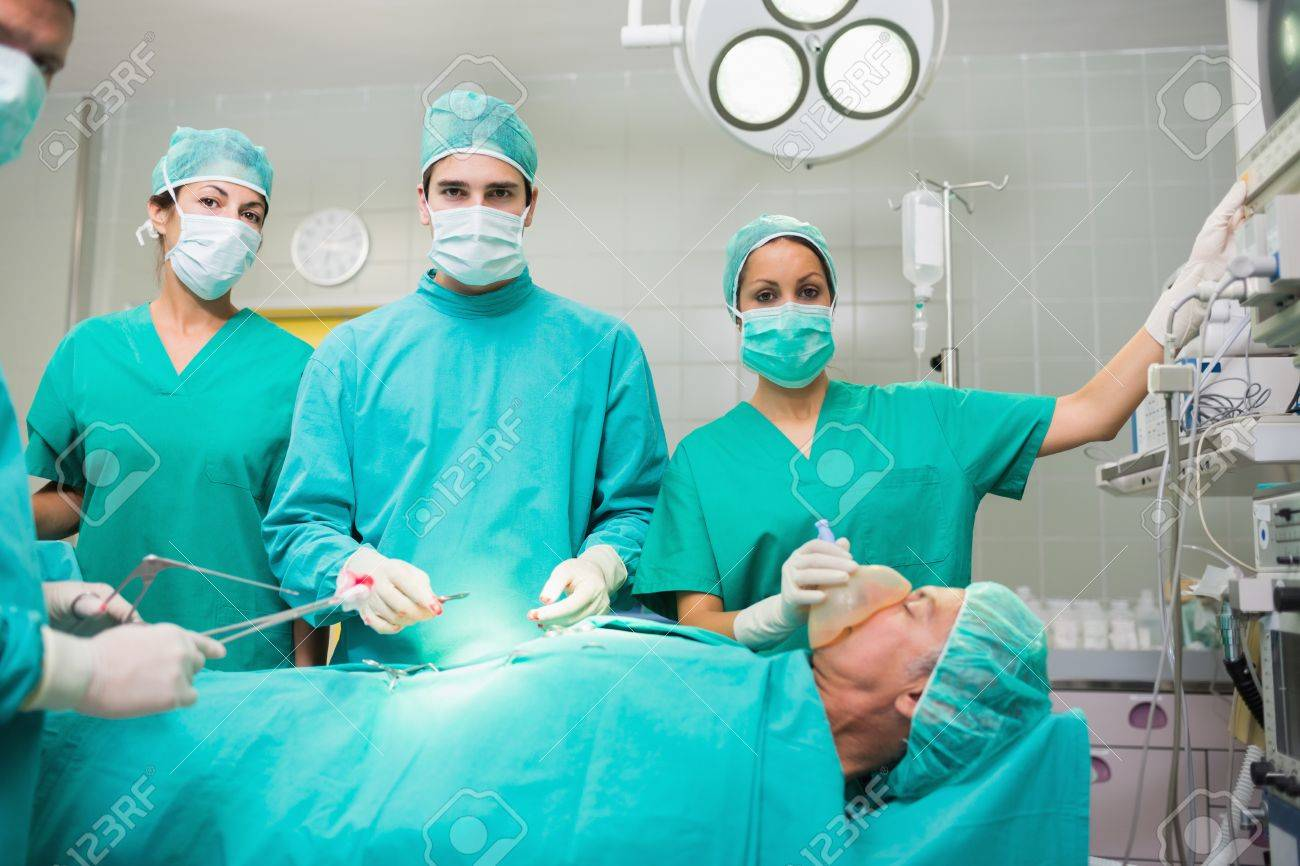 Surgical team looking at camera in an operating theatre Stock Photo - 16229041