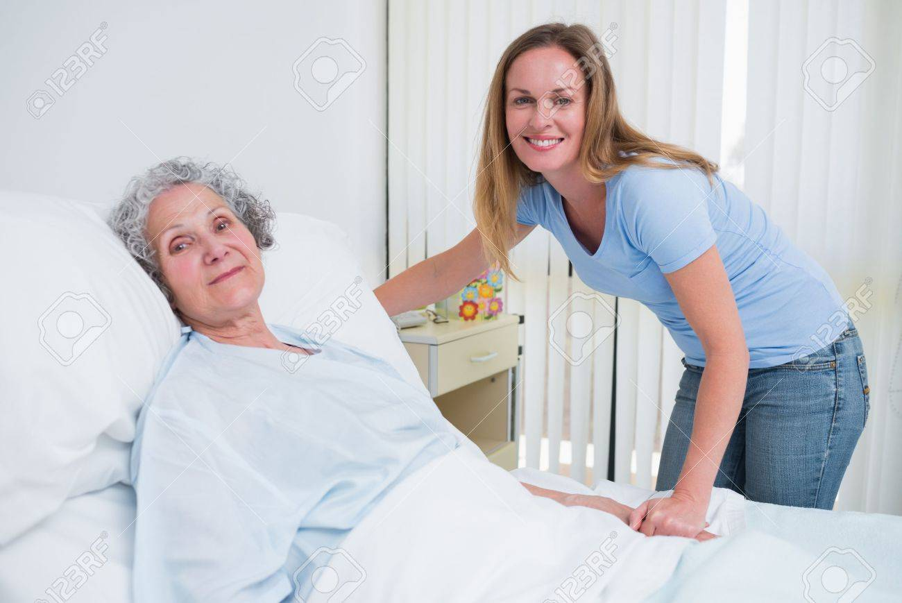 Woman holding the hand of a patient in a hospital room Stock Photo - 18095138