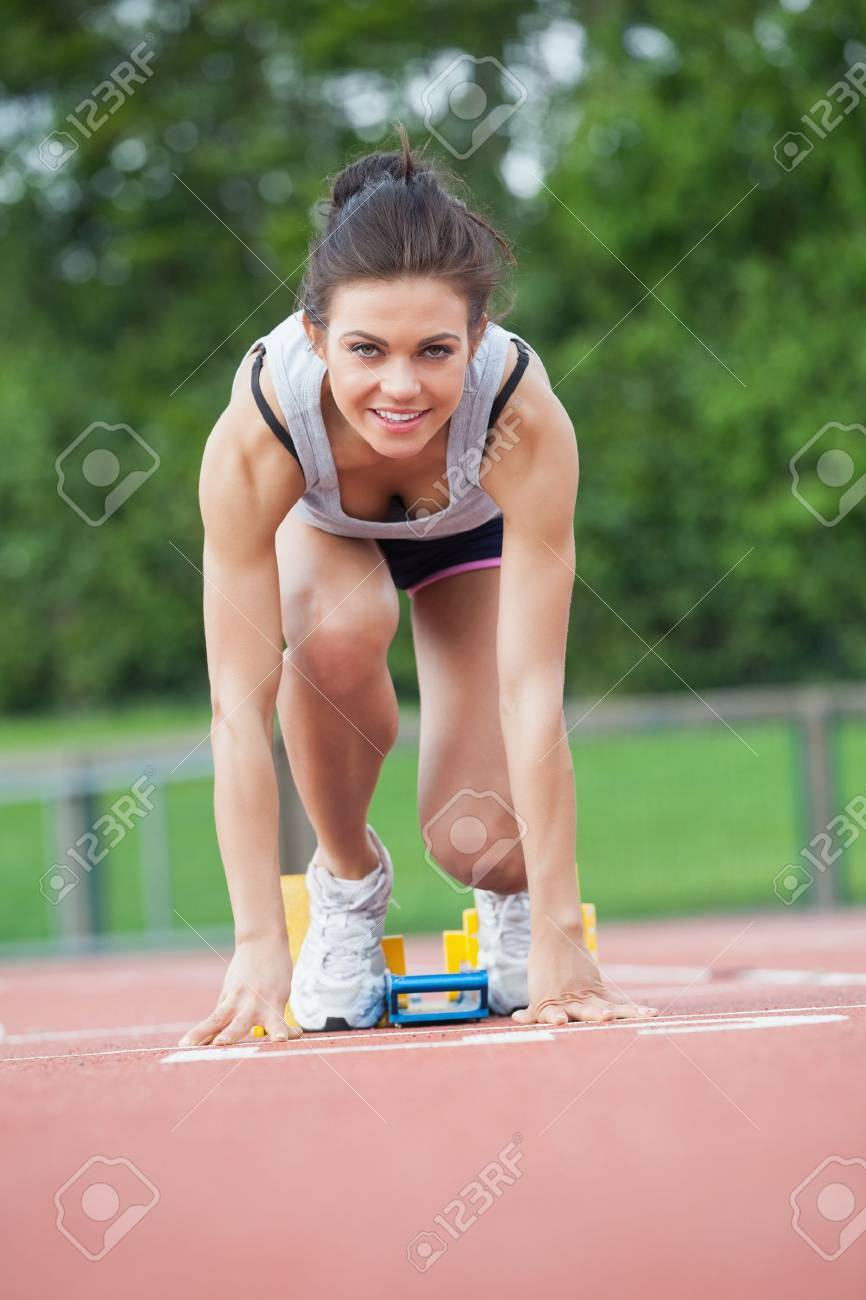 Female athlete at athletic starting blocks on track field Stock Photo - 18095230