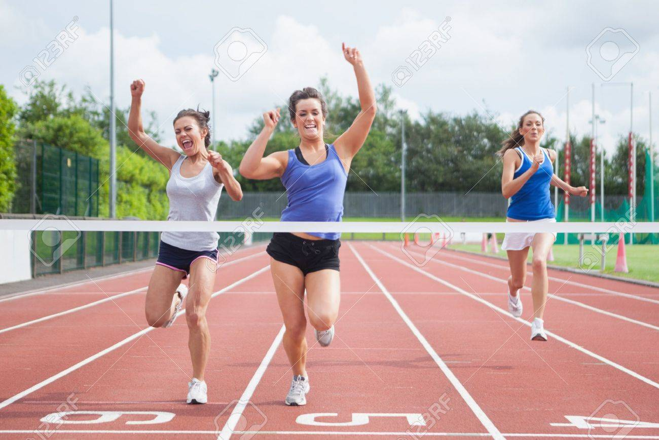 Female athletes celebrating as they cross finish line on track field Stock Photo - 18095060