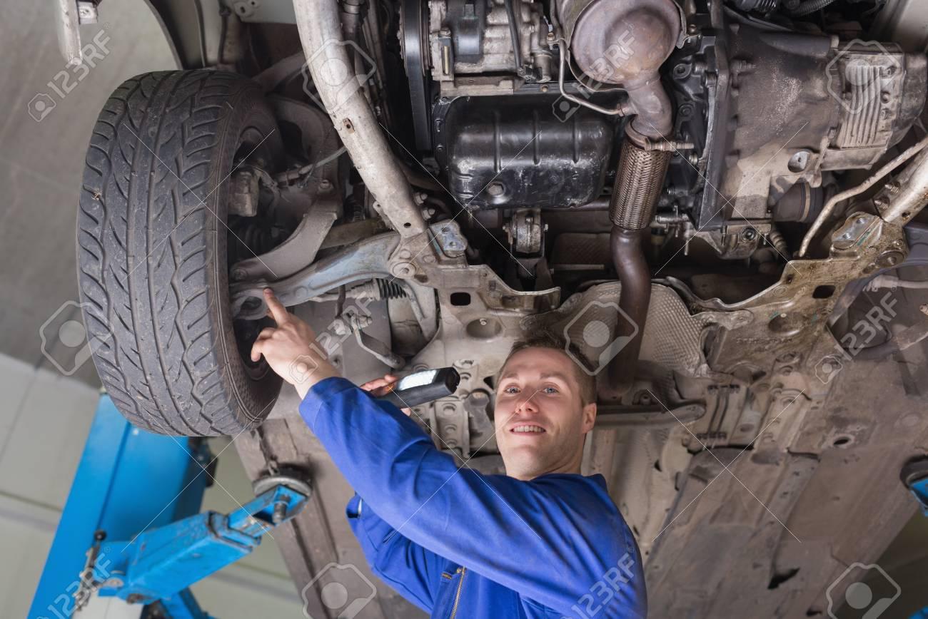 auto mechanic with flashlight examining car tire stock photo