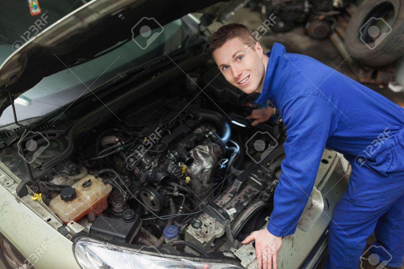 portrait of male mechanic with flashlight examining car engine stock