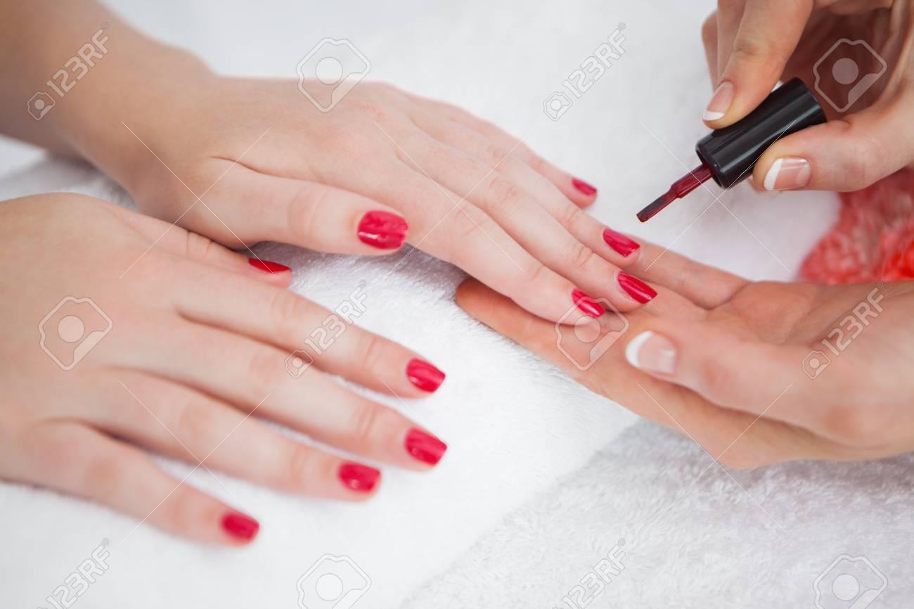 Close-up of woman applying nail varnish to finger nails at nail salon Stock Photo - 18124324