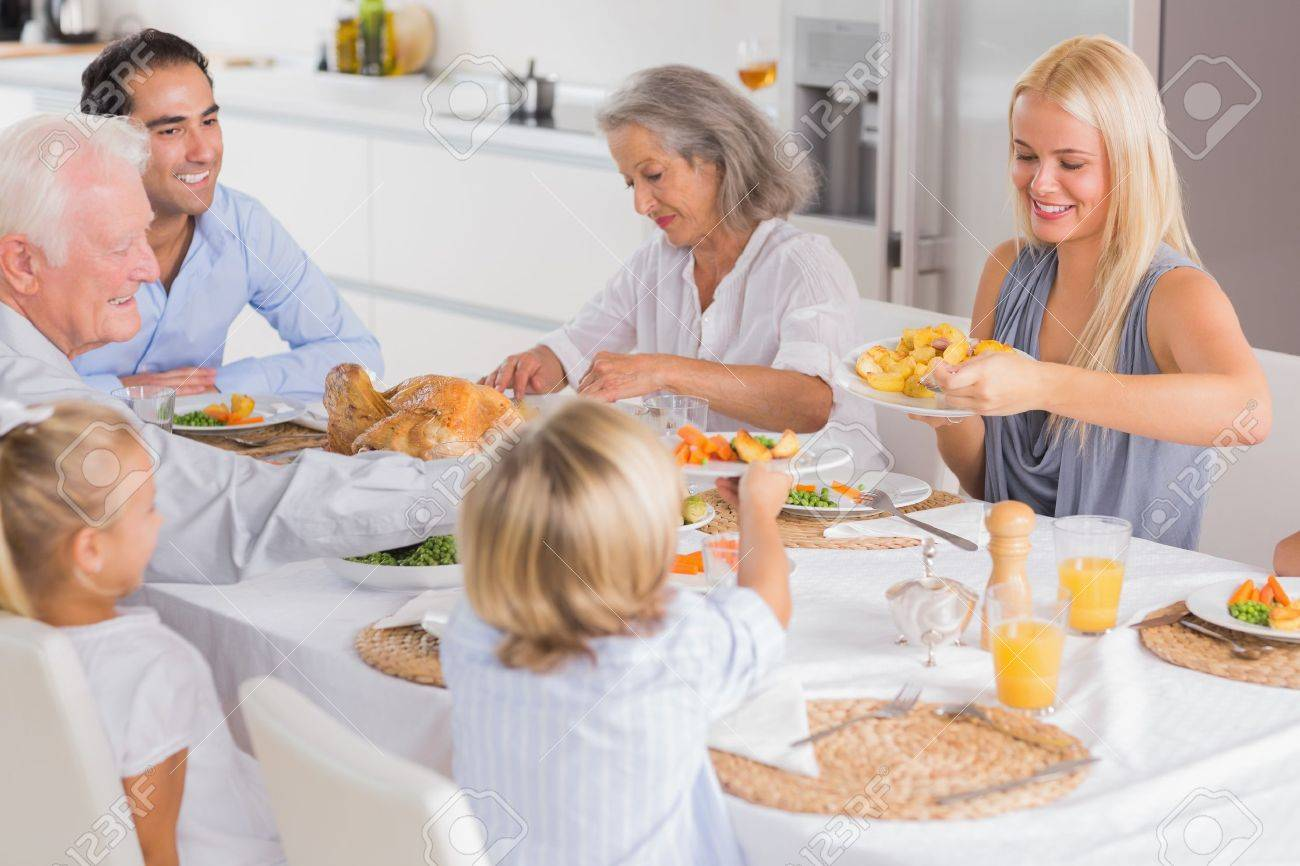 Happy Family Eating The Thanksgiving Dinner Together Stock Photo
