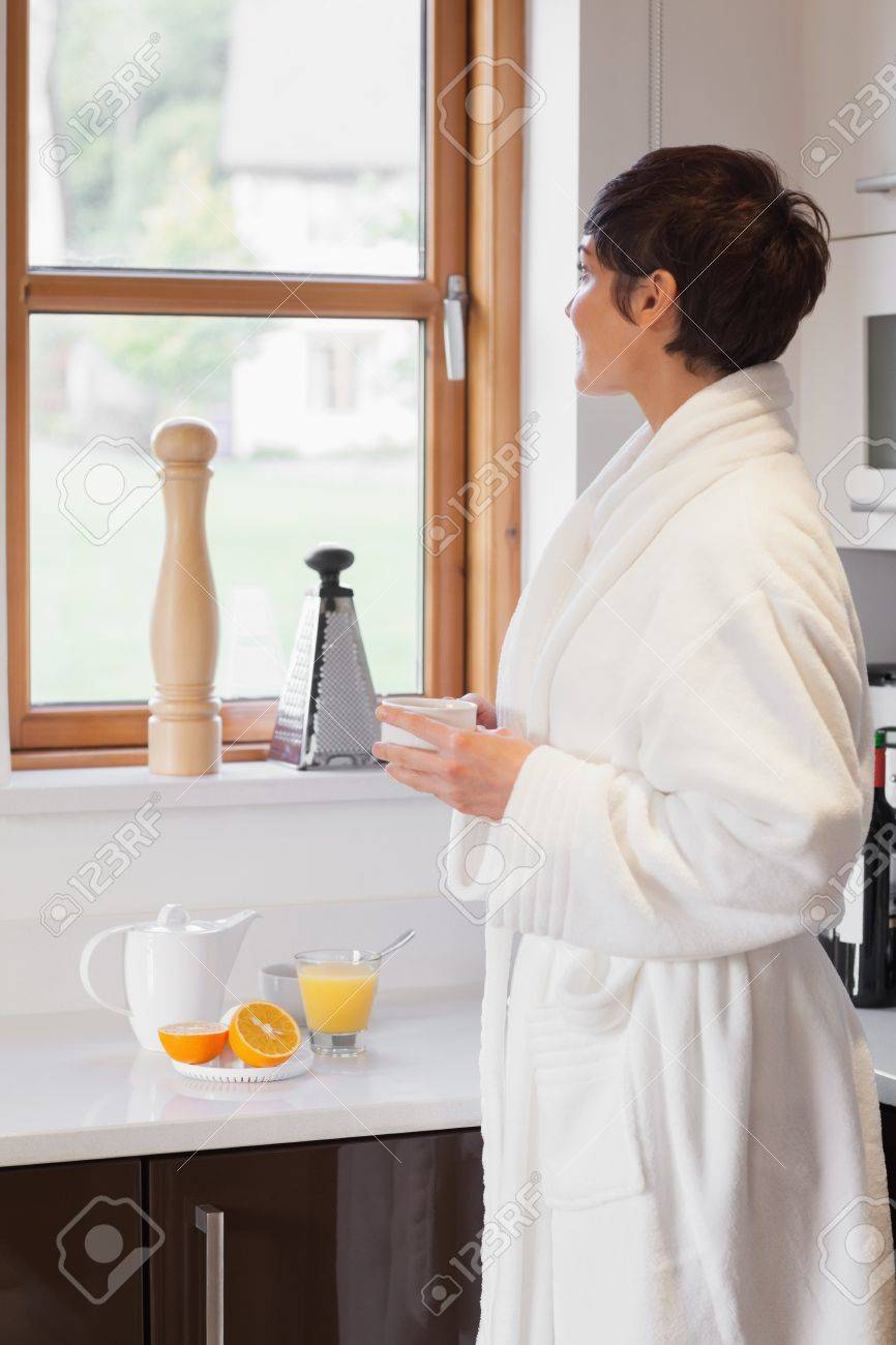 Woman In Bathrobe Looking Out Of Window With A Coffee In Kitchen ...