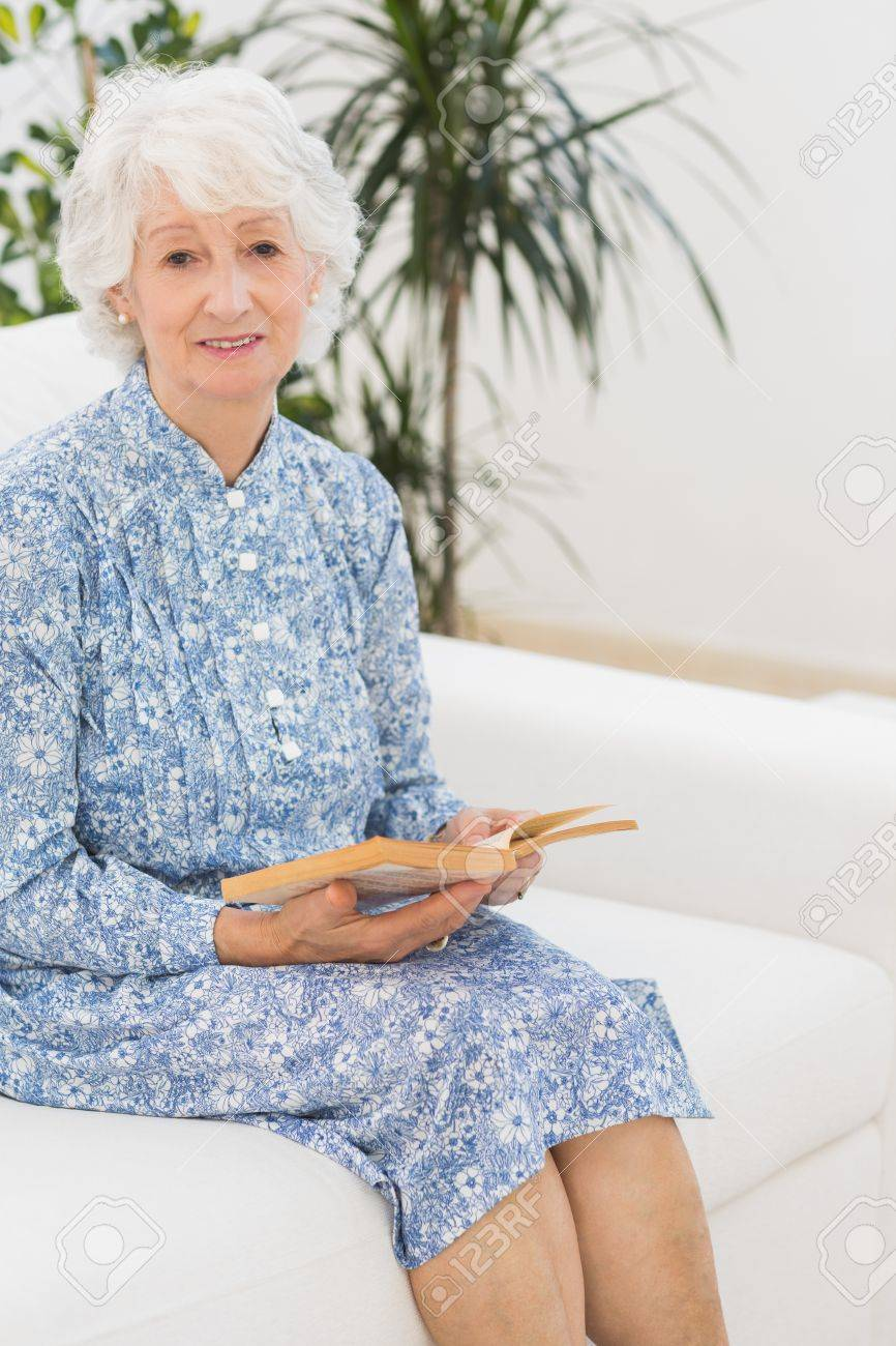 Elderly woman reading a old novel and looking at camera on a sofa Stock Photo - 18118252