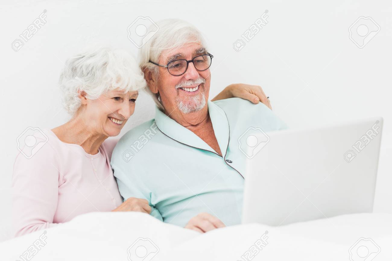 Elderly couple using laptop in bed Stock Photo - 18118383