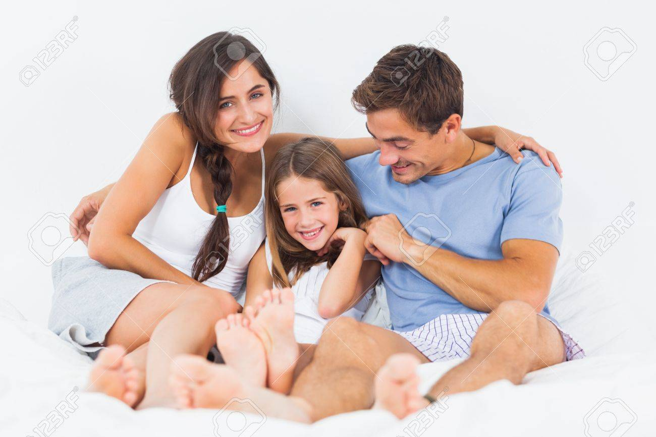 Joyful family sitting on the bed in the bedroom Stock Photo - 18121358