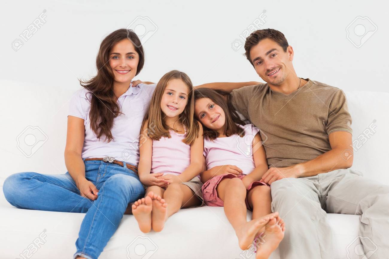 Cute Family Sitting On A Sofa In The Living Room Stock Photo   18121708