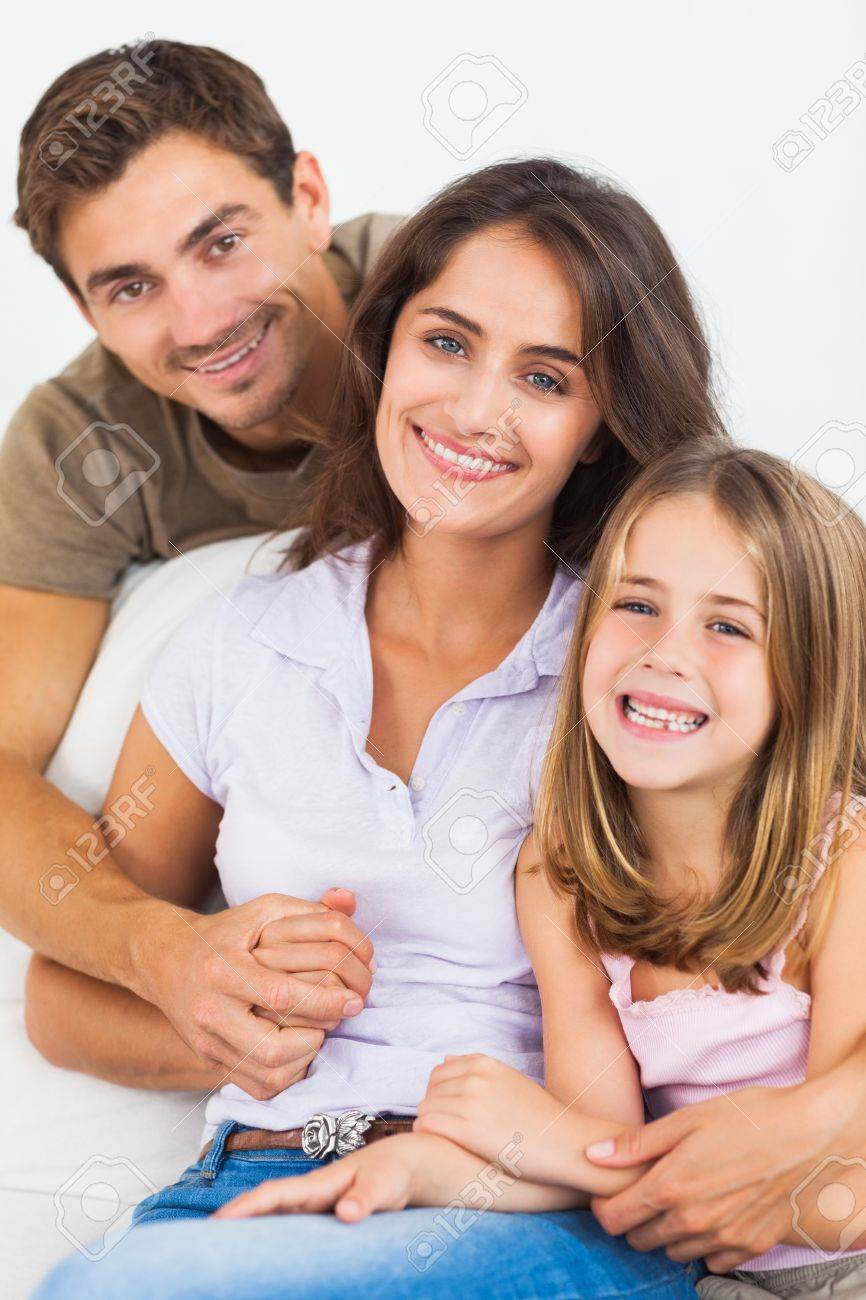 Parents and their daughter smiling on a sofa Stock Photo - 18122030