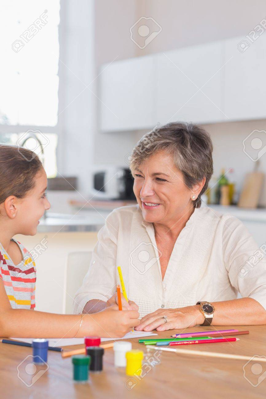 Smiling child with her granny drawing in kitchen Stock Photo - 18125864