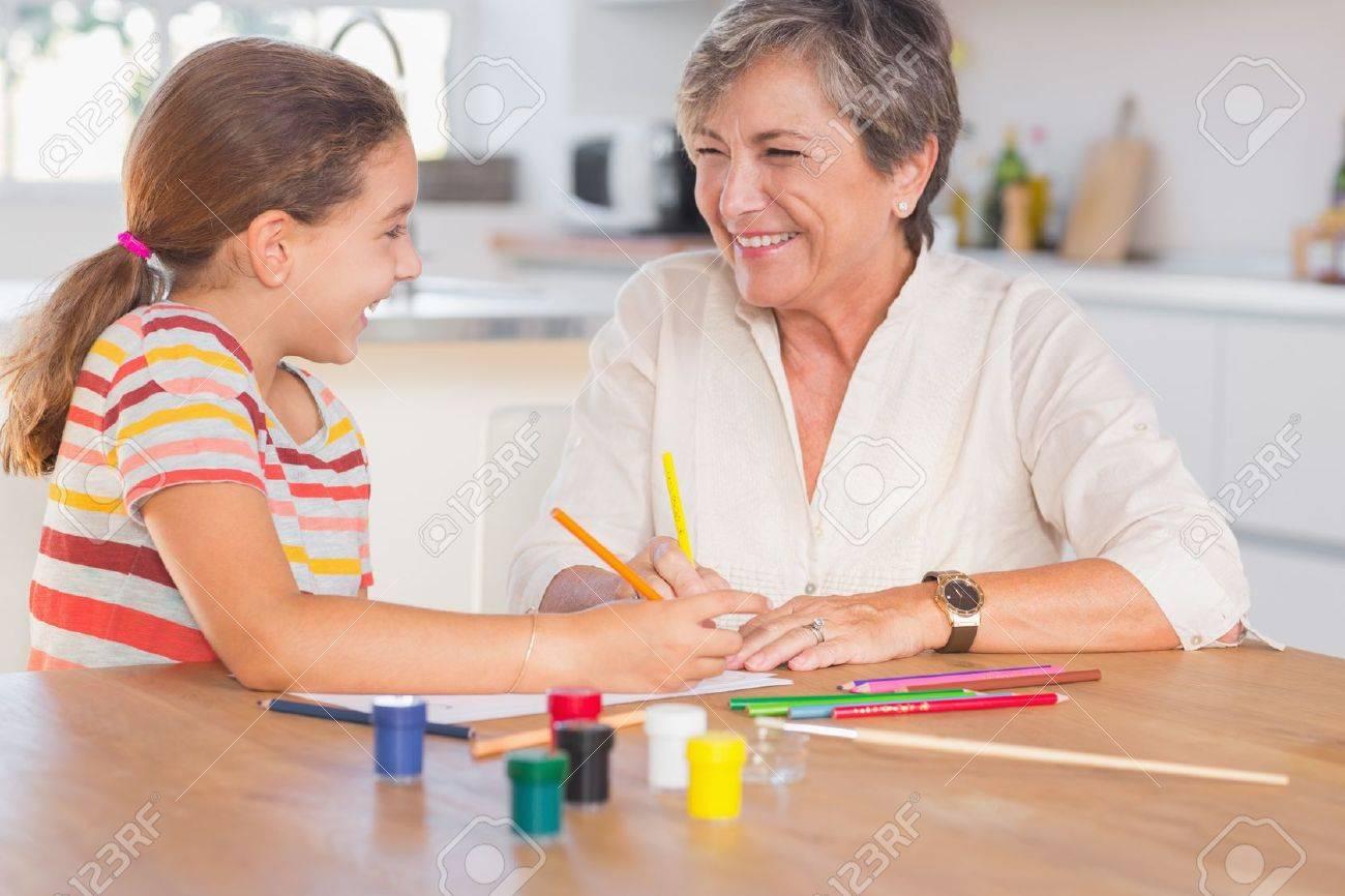 Kind Mit Ihrer Oma Zeichnen Und Lachend In Der Kuche Lizenzfreie