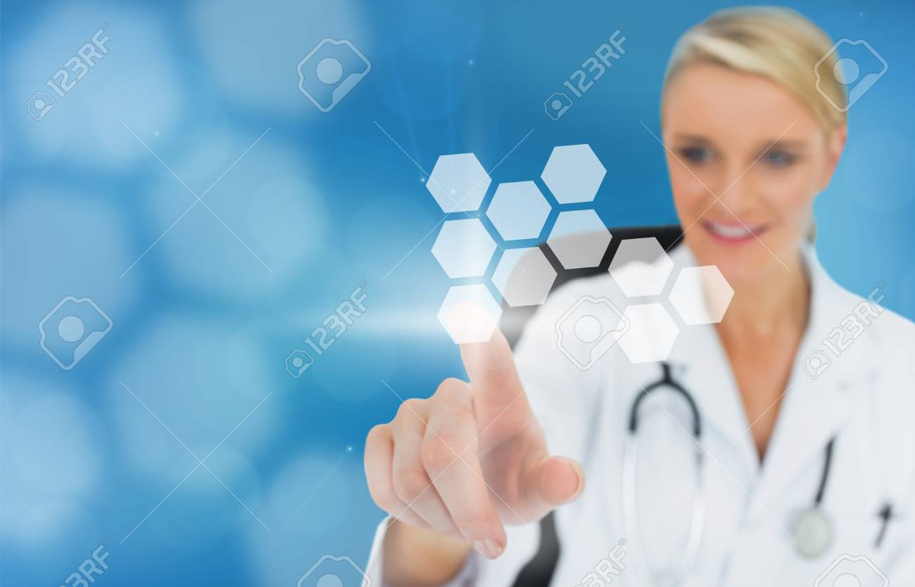 Blonde doctor using touchscreen displaying hologram on blue background Stock Photo - 18132139