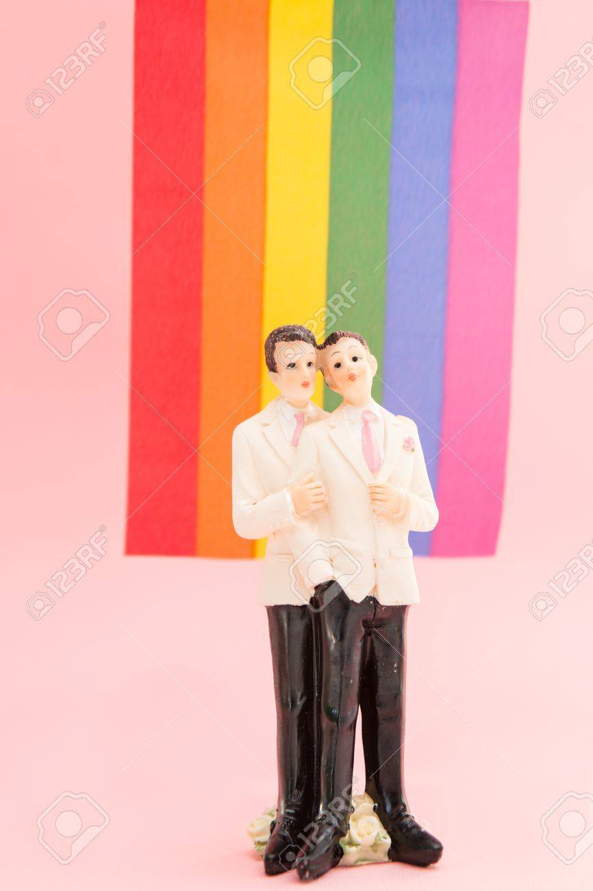 Gay groom cake toppers in front of rainbow flag on pink background Stock Photo - 18129721