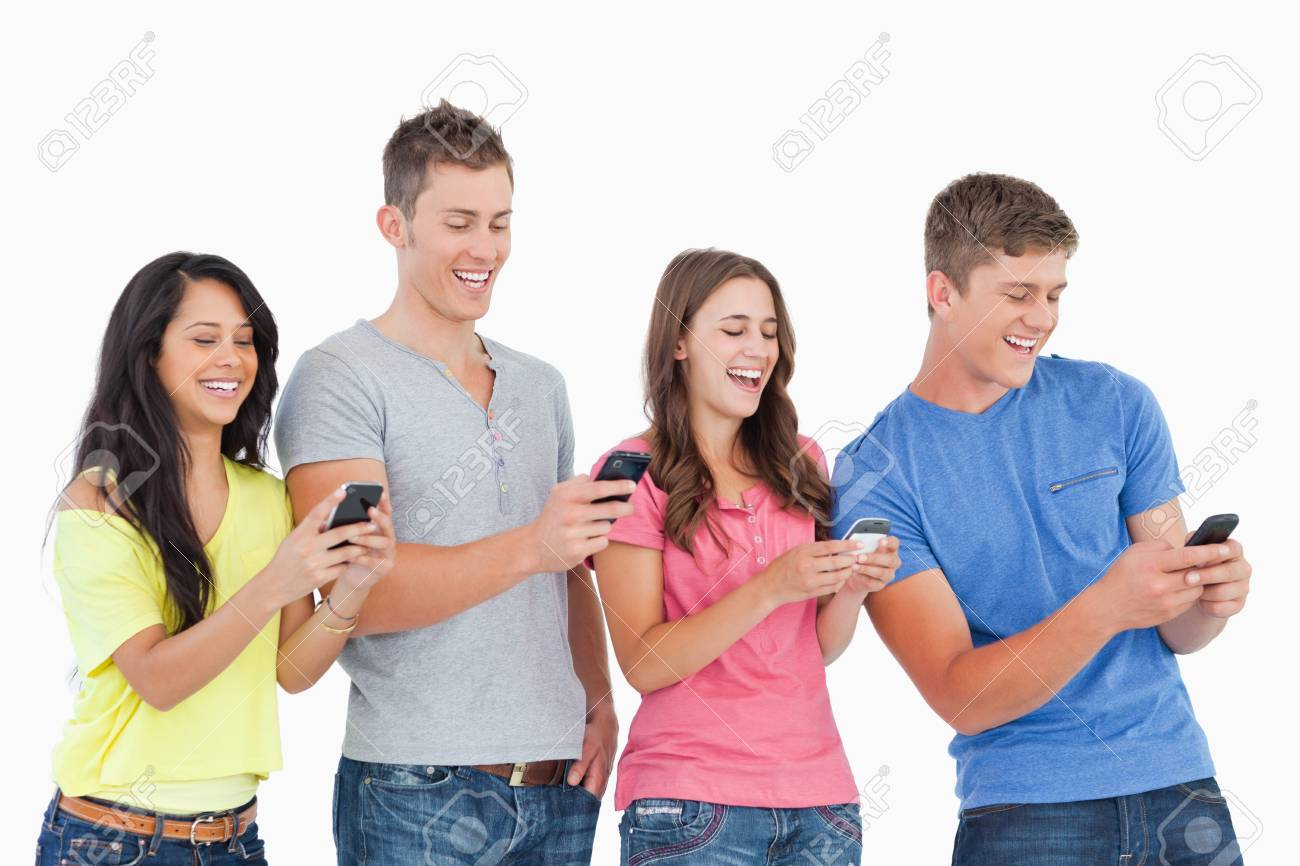 A group of friends laughing as they all send texts with their phones Stock Photo - 18683457