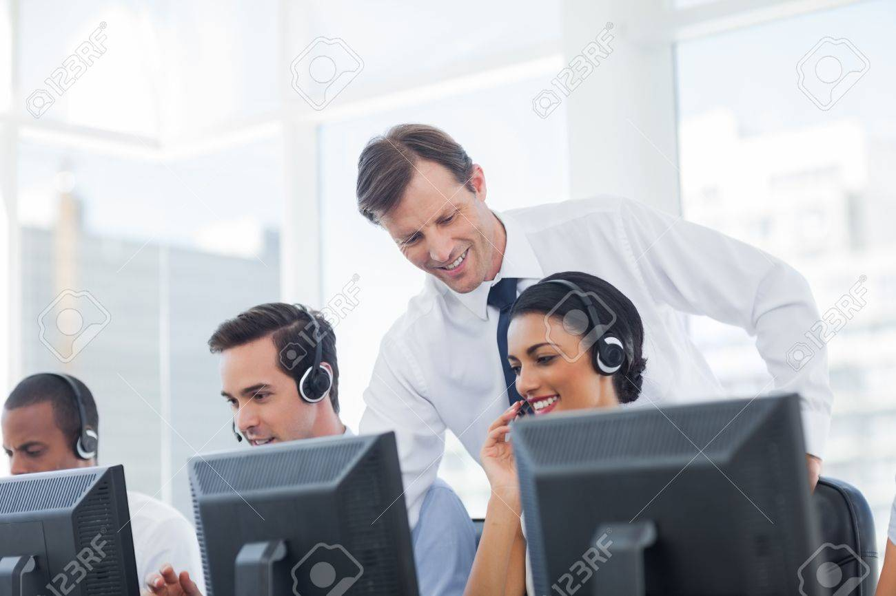 Manager listening to call centre employee working on computer Stock Photo - 20467840