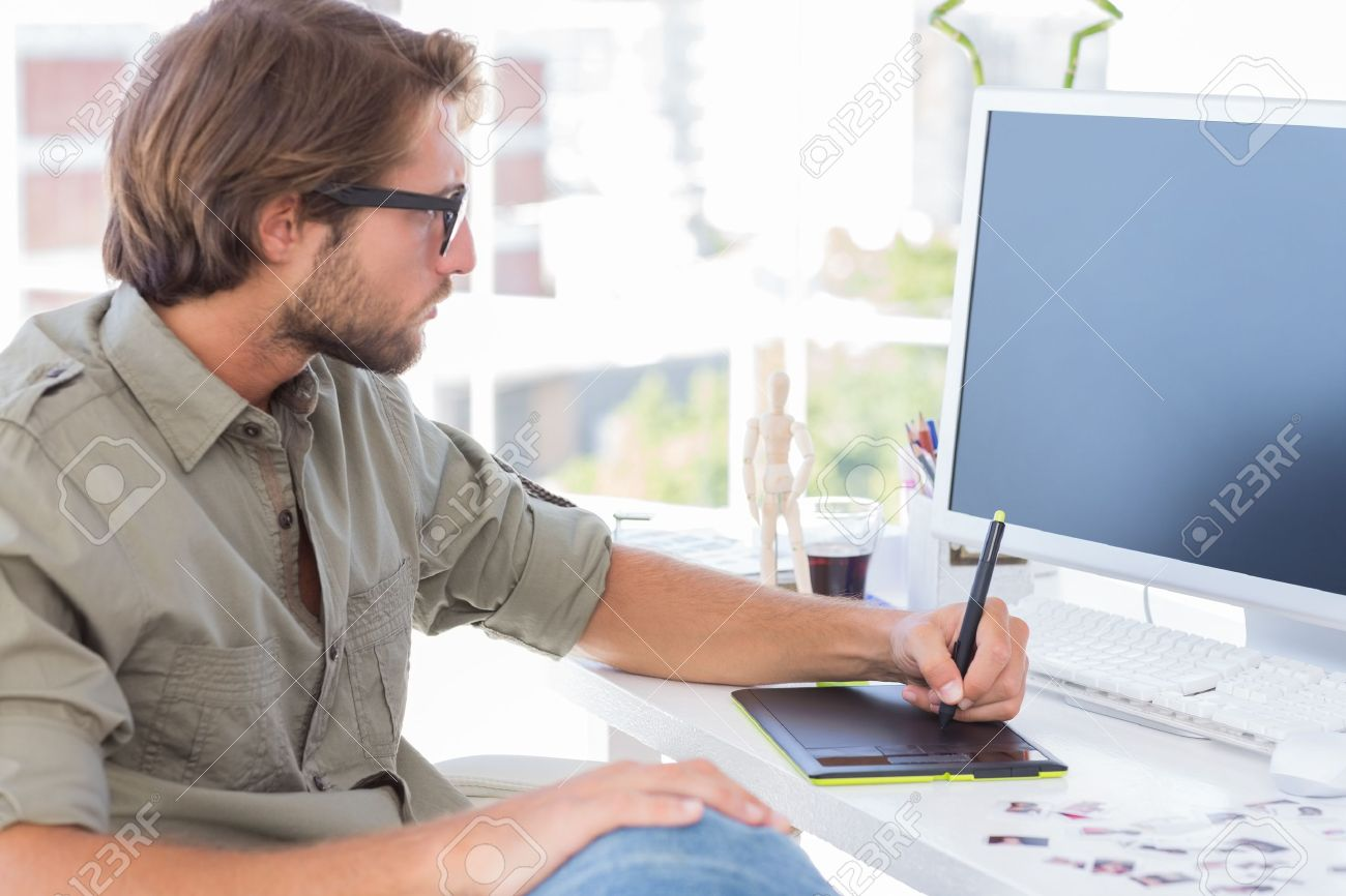 Artist using graphics tablets sitting at desk Stock Photo - 20501211