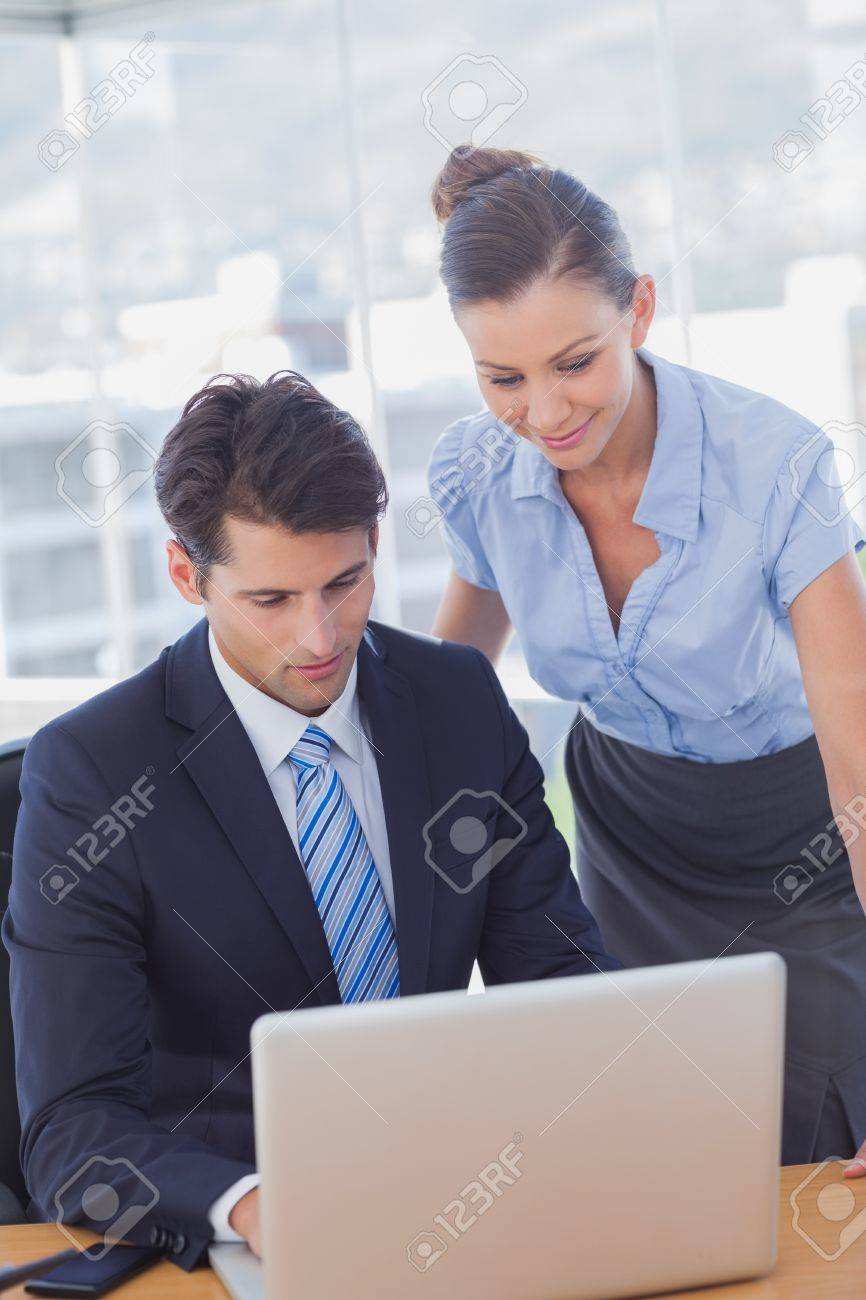 Business people smiling and working together with a laptop in the office Stock Photo - 20591644