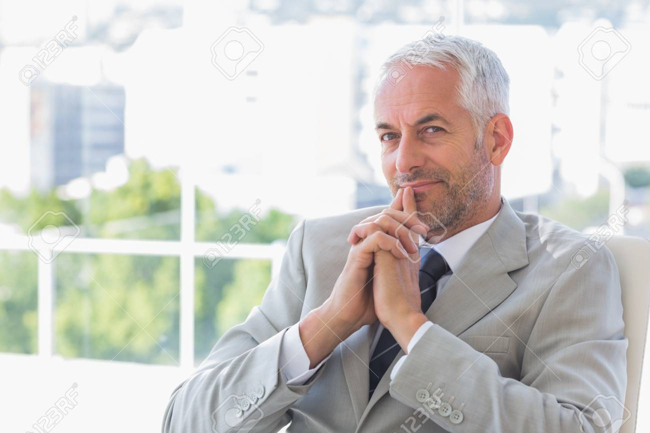 Happy businessman thinking in his office Stock Photo - 20586935