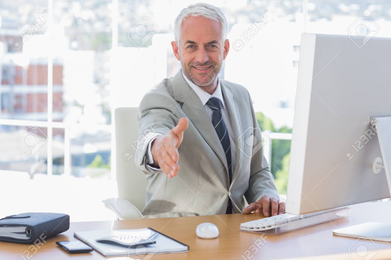 Smiling businessman reaching out arm for handshake at his desk Stock Photo - 20500551