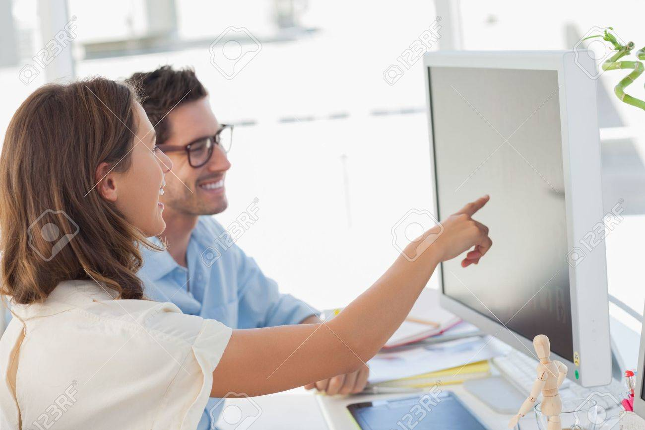 Attractive photo editor pointing at the screen while working with a colleague - 20586337