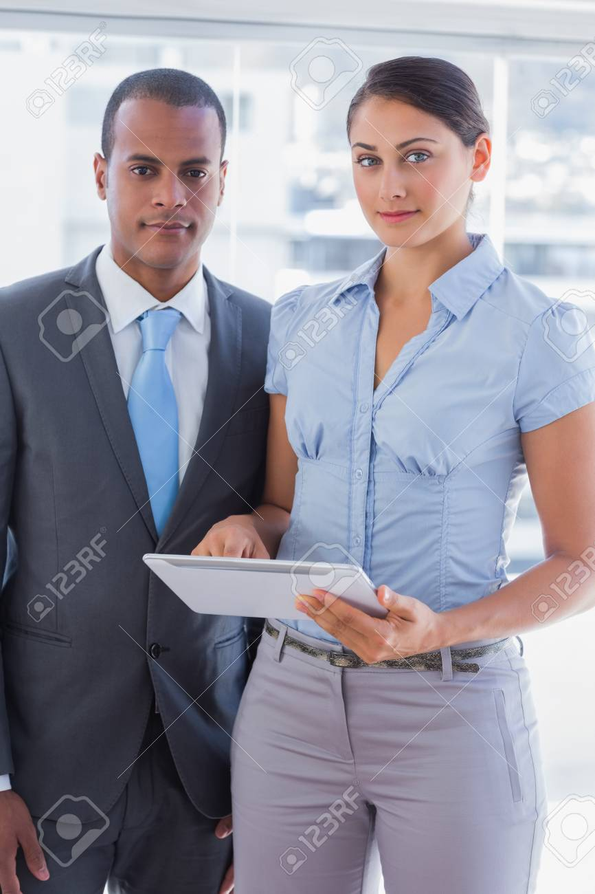 Business team with tablet pc smiling at camera standing in the office Stock Photo - 20617824