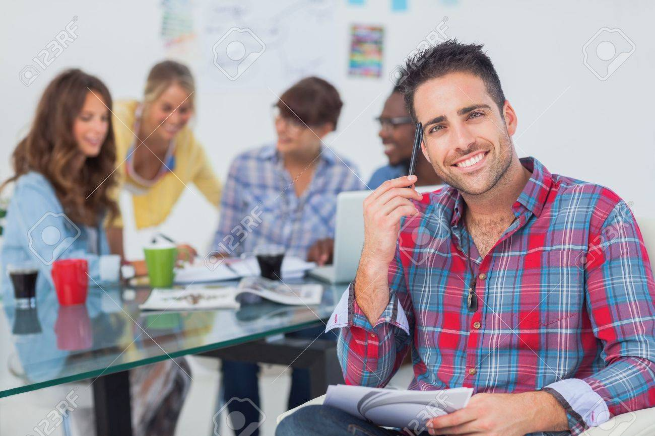Handsome designer sit in his office with colleagues discussing behind Stock Photo - 20640426