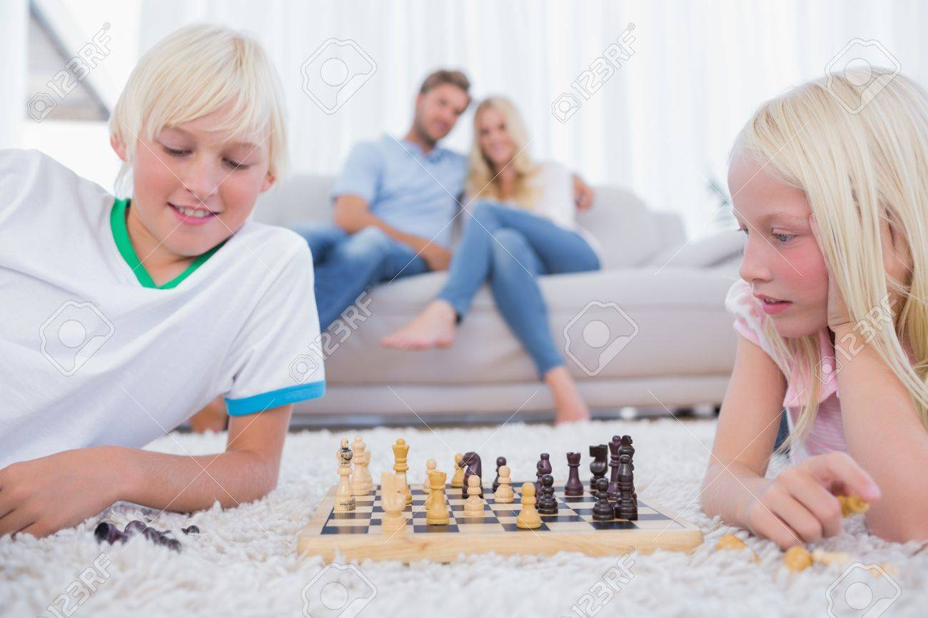 Two children playing chess in the living room Stock Photo - 20635986
