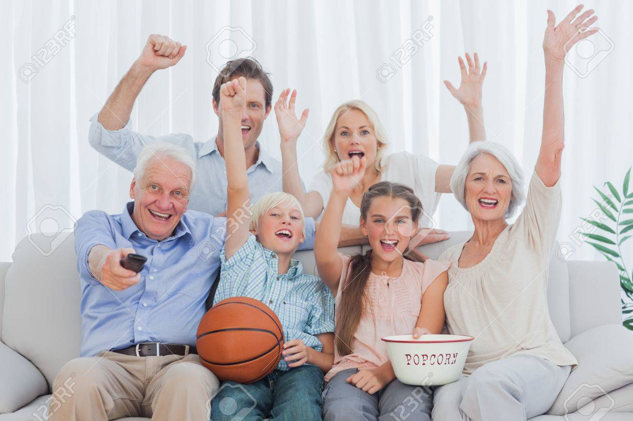 Extended family watching the tv on sofa Stock Photo - 20638442