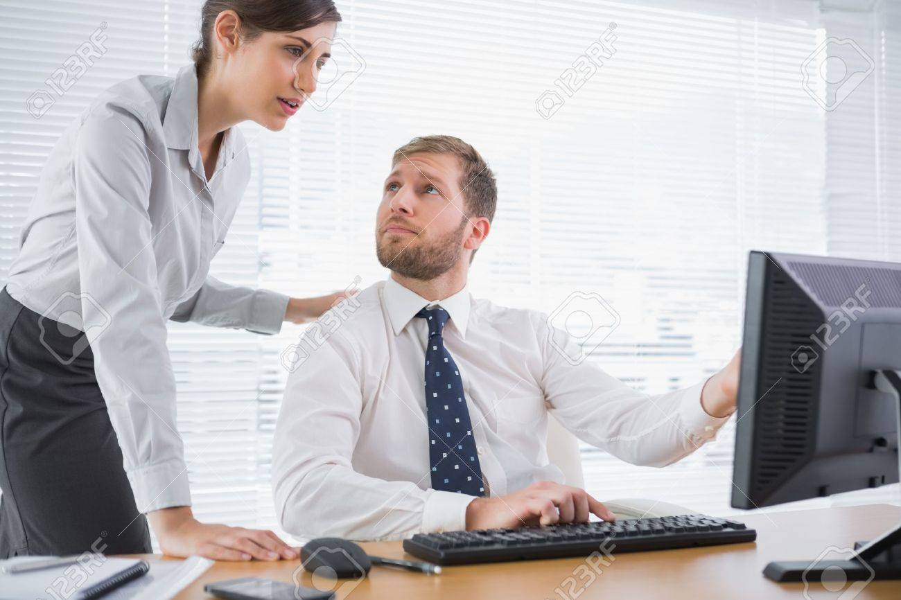 Businessman showing his co worker something on computer at his desk in office Stock Photo - 20635397
