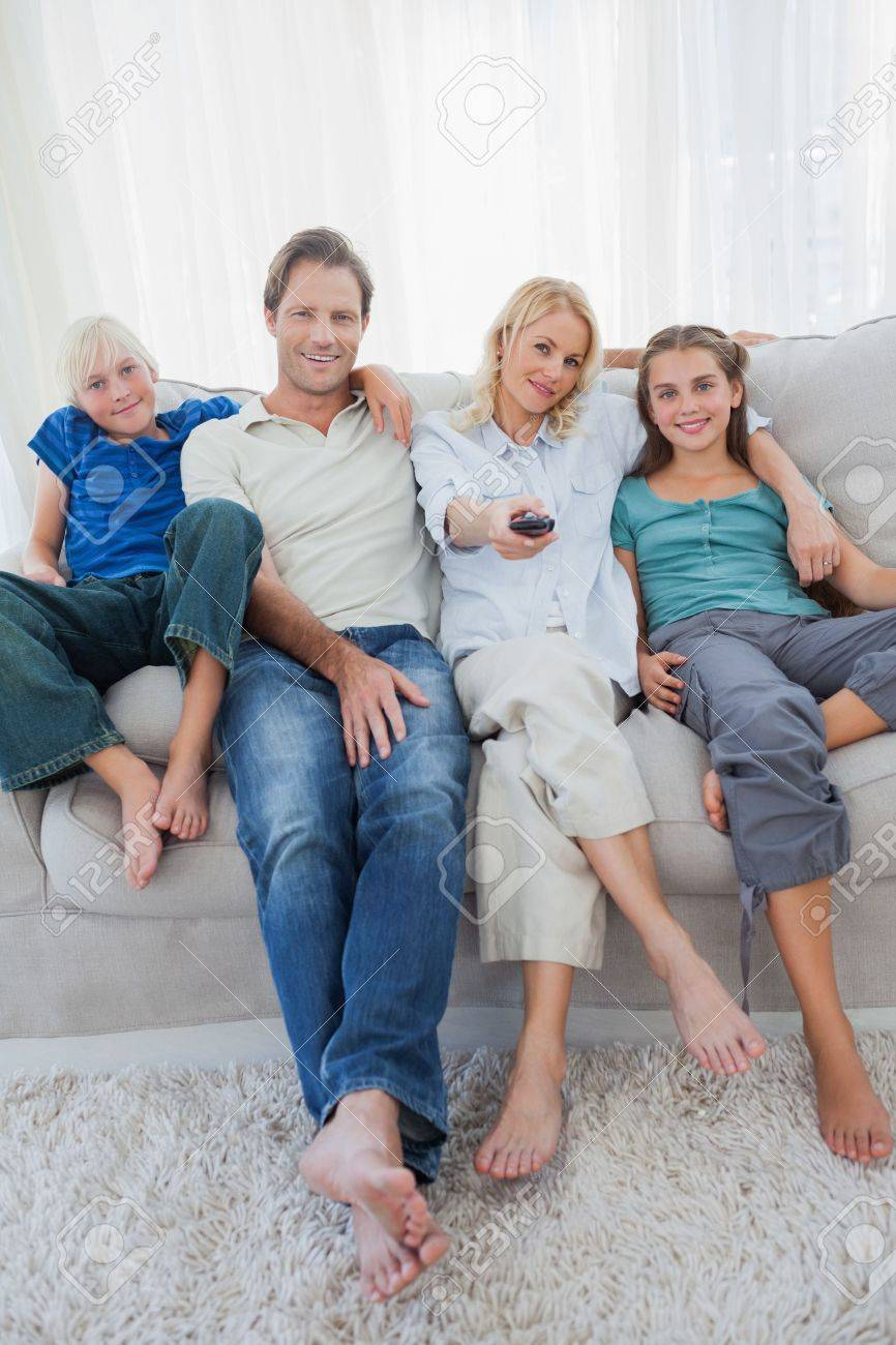 Portrait of a family watching television sitting on a couch Stock Photo - 20639714