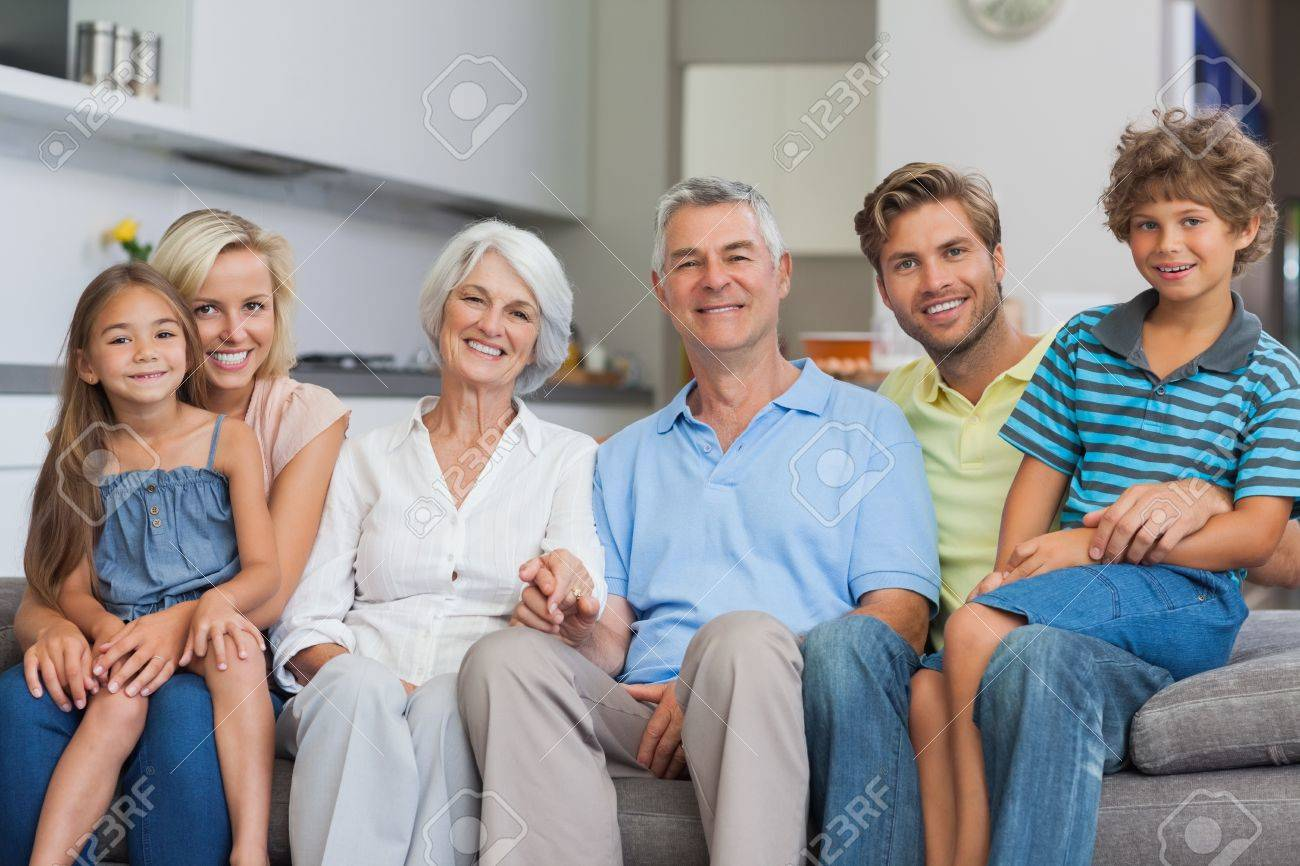 Extended family sitting on couch in living room and smiling at camera Stock Photo - 20640430