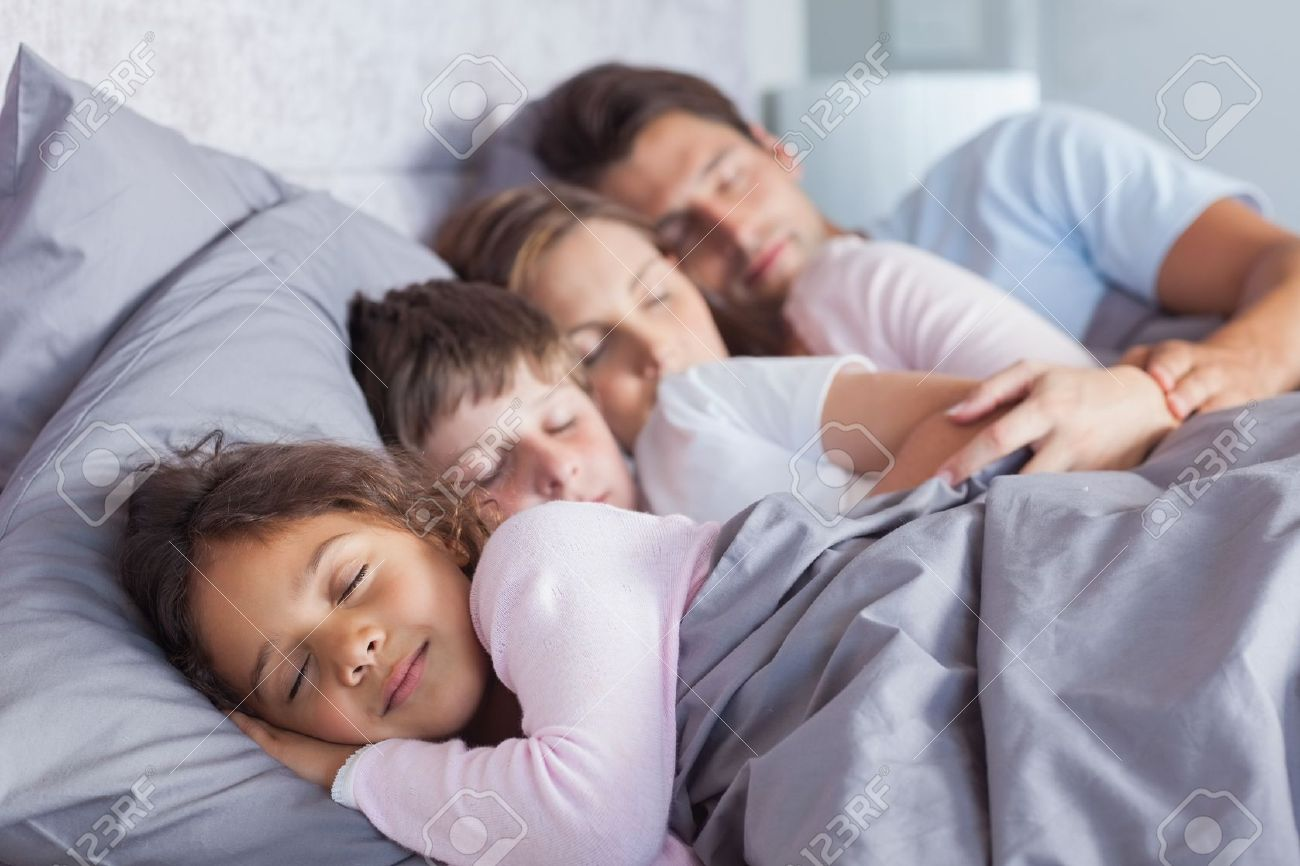 Cute family sleeping together in bed stock photo 20640603