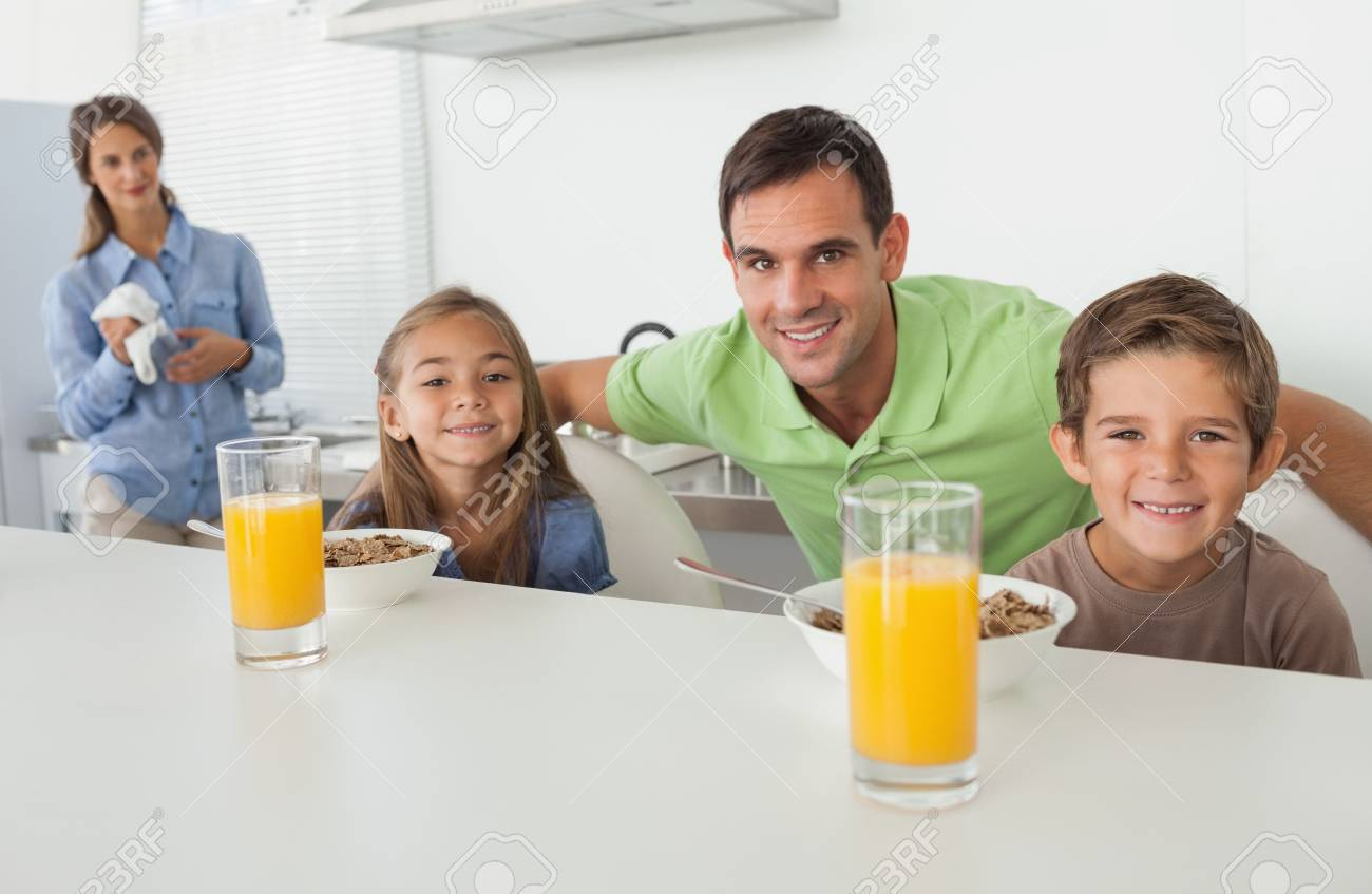 Portrait of a father and his children having breakfast with mother looking at them on the background Stock Photo - 20634692