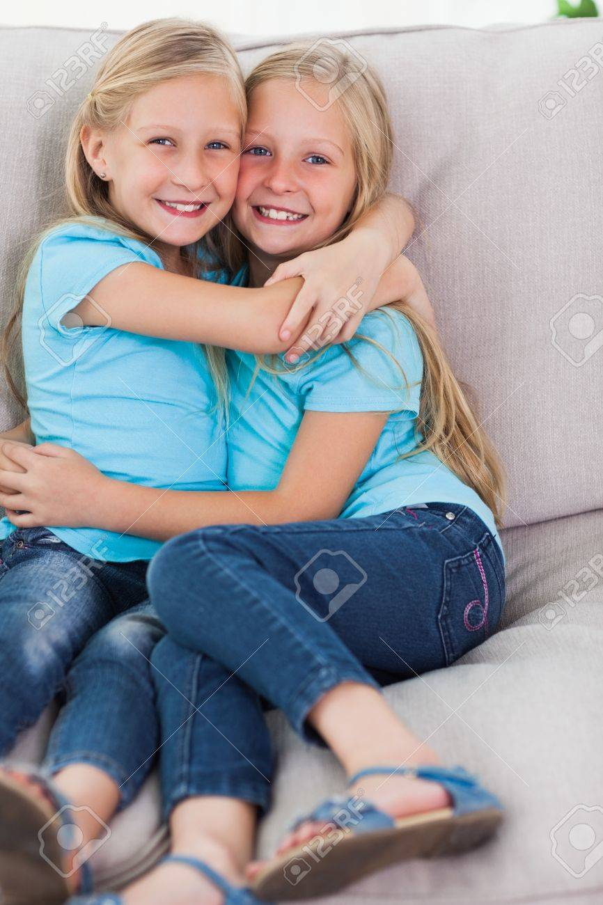 Young Twins Embracing Each Other On A Couch In The Living Room Stock