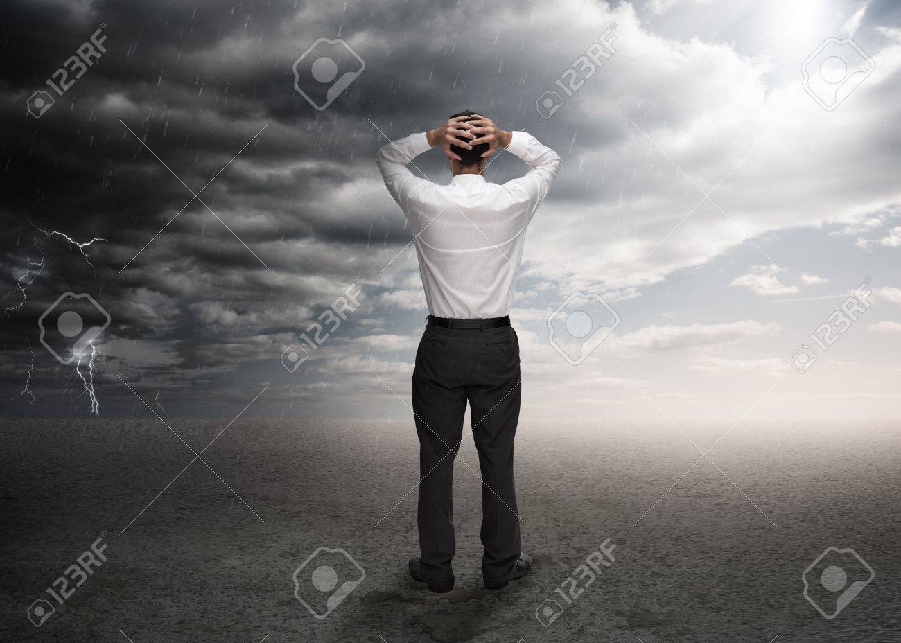 Businessman standing in a desert during a stormy weather Stock Photo - 20625385