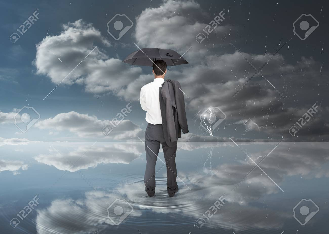 Businessman holding a black umbrella during stormy weather Stock Photo - 20625380