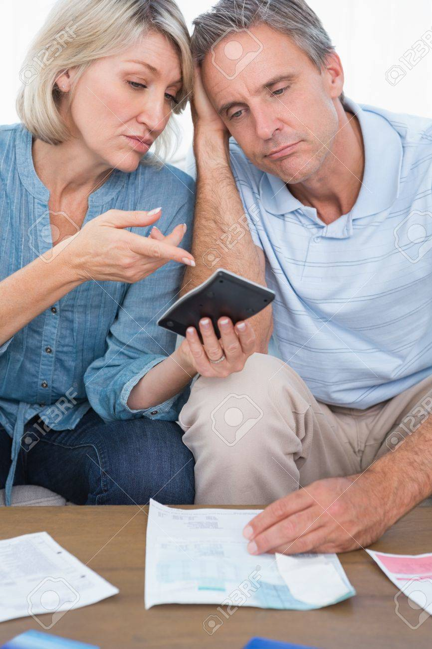 Anxious couple going over their debt at home in living room Stock Photo - 20626872