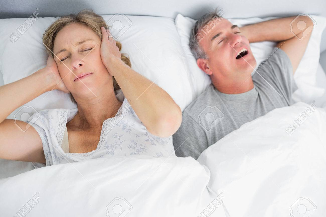 Stock Photo Wife blocking her ears from noise of husband snoring in bedroom  at home. Husband Wife Bedroom Images   thegibbonsschool com