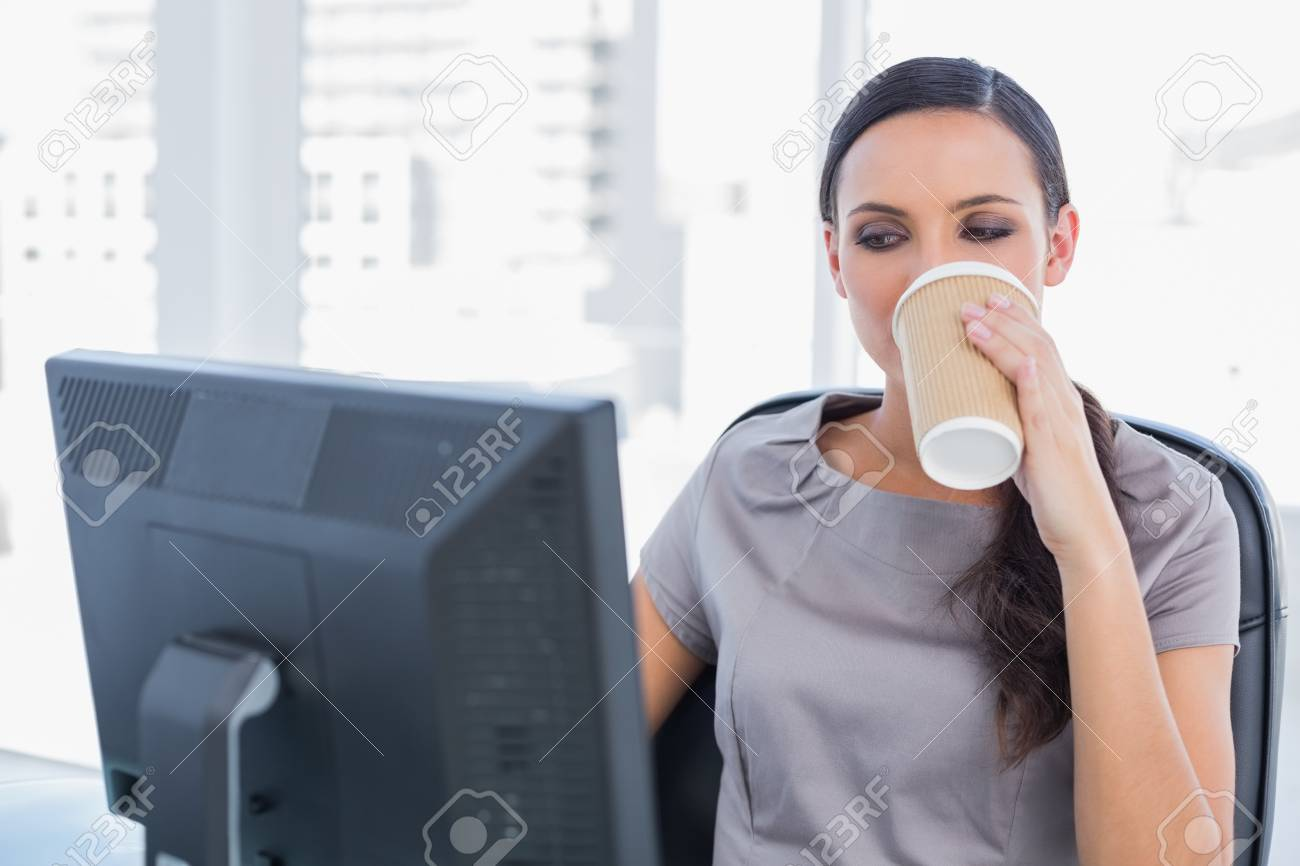 Attractive businesswoman drinking coffee and working in her office Stock Photo - 25741026