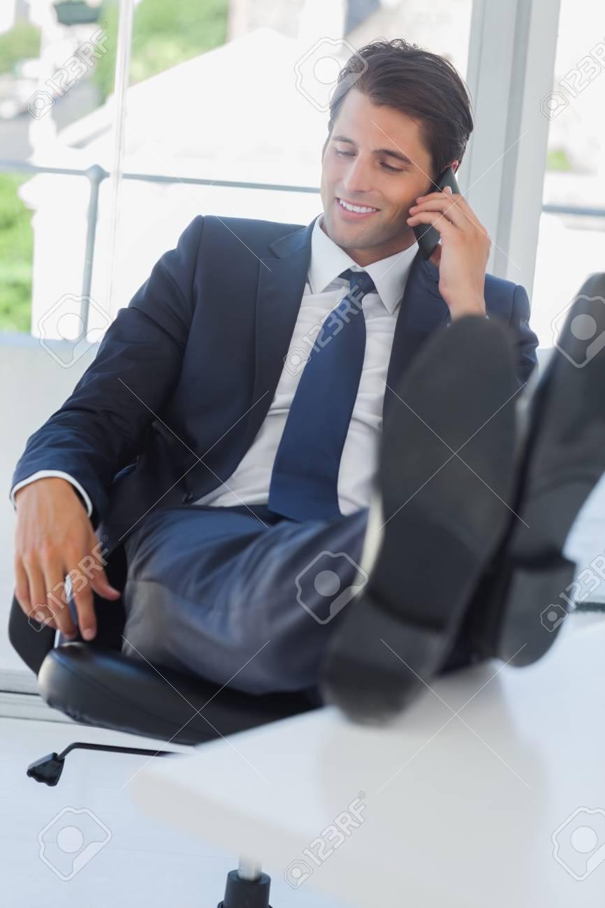 """Expresa tu momento """" in situ """" con una imagen - Página 38 25765283-hombre-de-negocios-en-el-tel%C3%A9fono-en-su-oficina-de-relax-con-sus-pies-sobre-su-escritorio"""